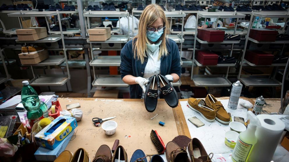 lady in factory holding shoes