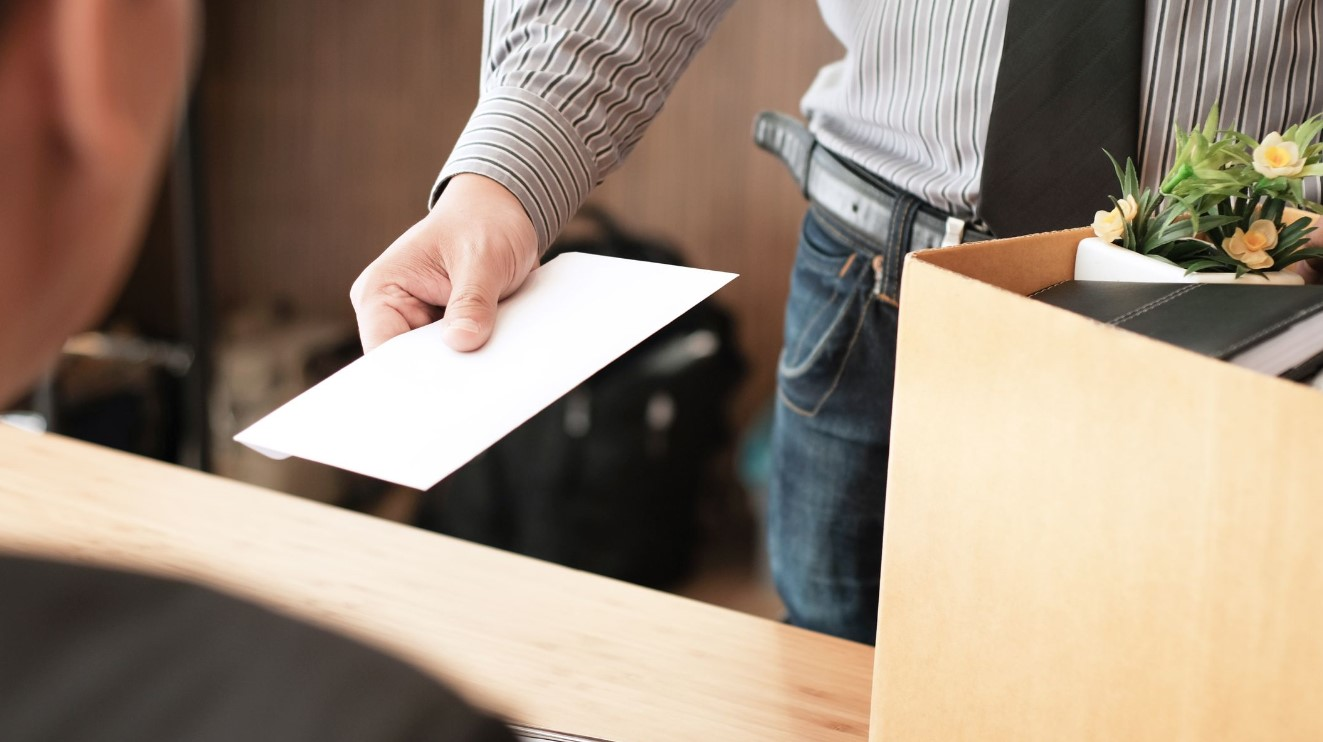mans hand passing a letter