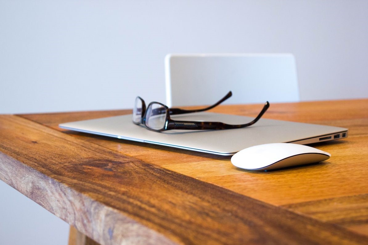 laptop, glasses and computer mouse sitting on table